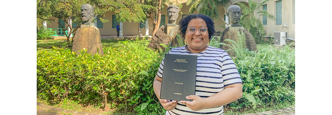 Mayra París Osorio proudly displays the final copy of her thesis.